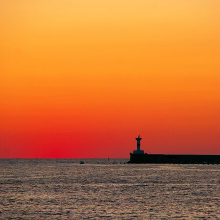 Silhouette of lighthouse against red sky at dusk. Sea shore landscape at sunset.