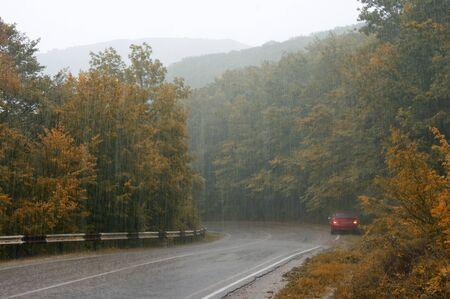 Asphalt road with car in aunumnal forest to heavy shower rain. Banco de Imagens