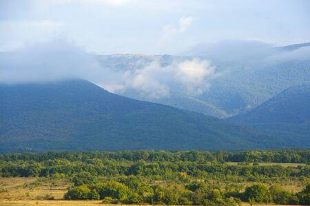 Sunny valley among foggy mountains. Banco de Imagens