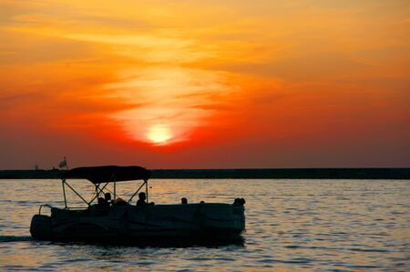 Silhouette of pleasure boat against red cloudy sky with sun. Sea shore landscape at sunset.