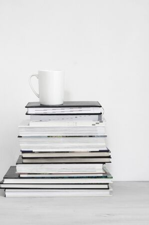 Mug of coffee on stack of books against white background.
