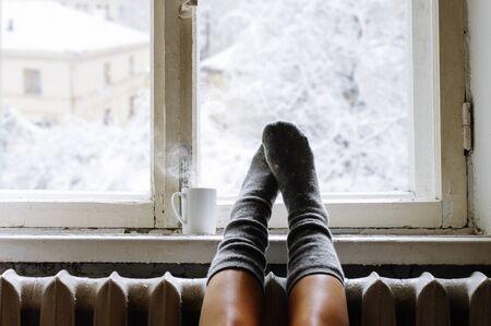 Cozy winter still life: woman legs in warm woolen socks and mug of hot beverage on old windowsill against snow landscape from outside. Reklamní fotografie
