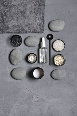 Composition of natural organic cosmetics, pebble and terry towel on grey background. Top view point, flat lay.