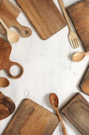 Set of various kitchen utensils - wood cutting boards, spoons and fork on rustic white wooden background. Top view, flat lay.