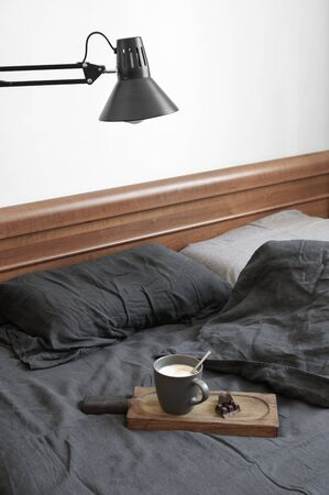 Unmade bed with dark grey linen bedding,  mug of coffee on wood tray and lamp. Banco de Imagens