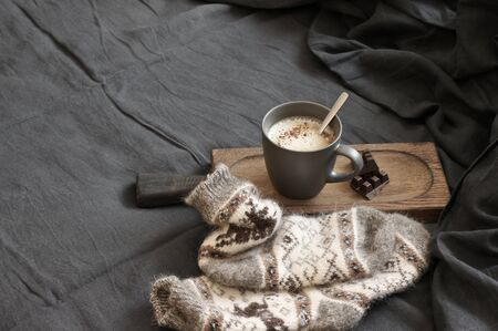 Mug of coffee latte with chocolate on wooden tray and warm woolen socks in unmade bed with dark grey linen bedding. Banco de Imagens