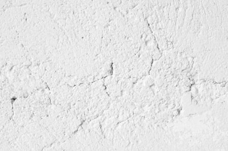 White distressed rough whitewashed wall texture as background.