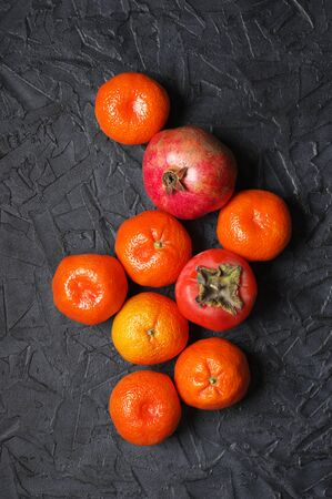 Tangerines, persimmon and pomegranate on black background. Mixed orange fruits, top view point.