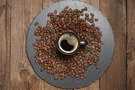 Black cup of coffee in coffee beans on slate dish on wooden table. Top view point.