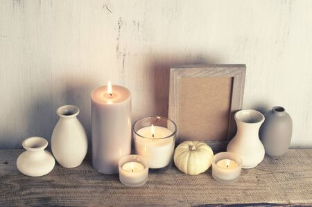 Neutral colored vases, burned candles and empty frame on rustic wooden shelf against shabby white wall. Home decor. Stock fotó
