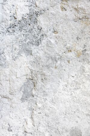 Distressed rough concrete whitewashed wall texture as background.