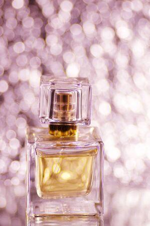 Woman perfume bottle on pink blurred glittering background. Stok Fotoğraf
