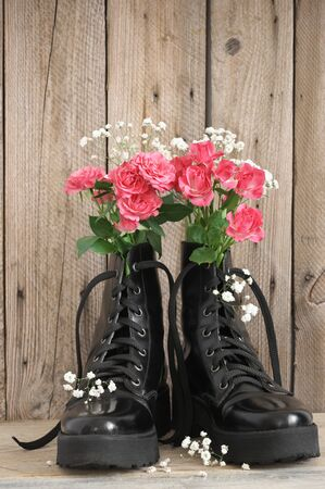 Bunch of flowers in black combat boots on rough wood background.