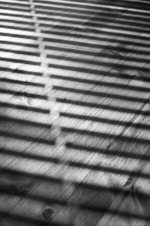 Striped lights and shadows pattern on rustic old distressed wood table at sunny day. Soft focus. Black and white image. Фото со стока
