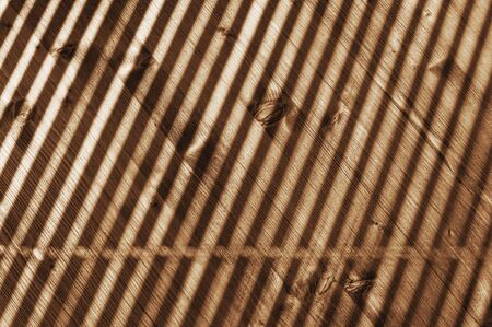 Striped lights and shadows pattern on rustic old distressed wood table at sunny day.