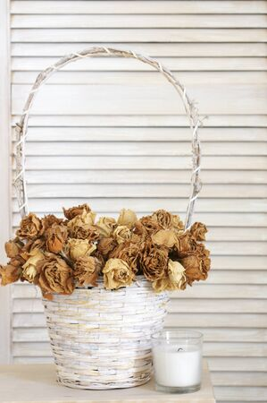 Dried roses in white basket and candle against rustic wood shutters. Shabby chic interior decor.