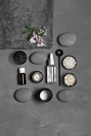 Composition of natural organic cosmetics, pebble, terry towel and flower on grey background. Top view point, flat lay.