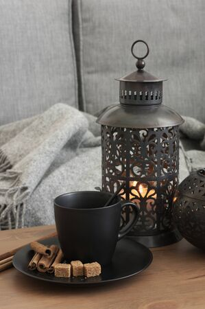 Black coffee mug and handmade metallic lanterns on wood table against gray sofa with blanket. Cozy living room, home interior decor.