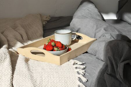 Unmade bed with breakfast on wood tray in sunlight. Good morning concept.