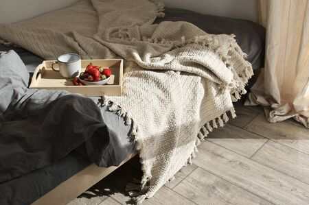 Unmade bed with breakfast on wood tray in cozy simple bedroom at sunlight. Good morning concept. Stock Photo