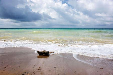 Stormy sea by sand beach.
