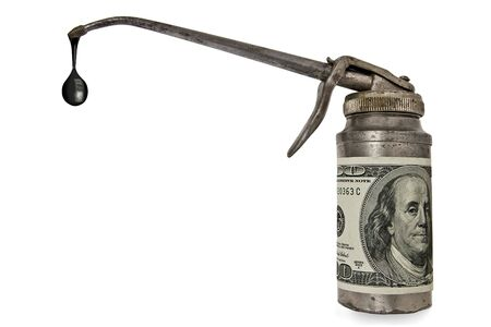 vintage oil can with $100 bill as a label over white Imagens