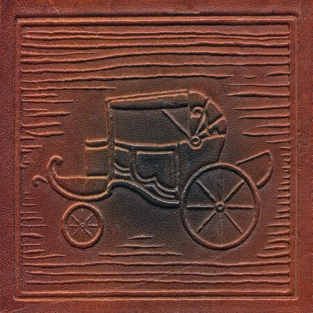 vintage leathercraft tooled book cover with texture and carriage silhouette Stock Photo