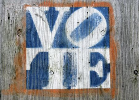 election vote: faded colors vote sign on a weathered gray plywood