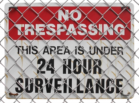 trespassing: no trespassing sign  on the fence, warning about surveillance