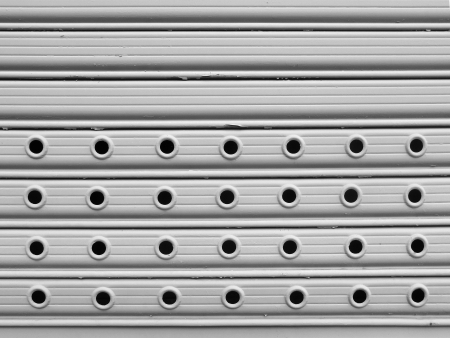 perforated: light grey painted perforated roll up gates background