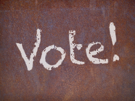faded color vote sign on a weathered rusty metal plate