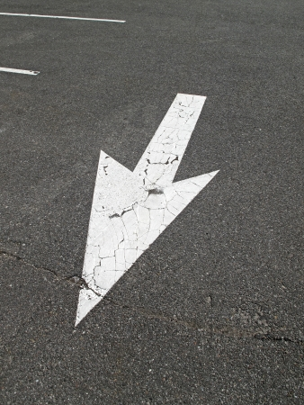arrow sign on the parking lot pavement photo