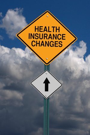 health risk: health insurance changes ahead road sign over dark sky with clouds