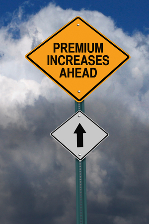 premiums: premium increases ahead road sign over dark blue sky with clouds