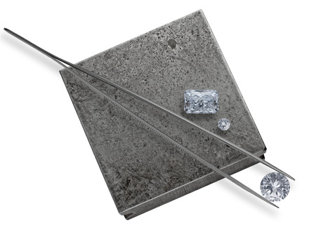 various cut cluster of diamonds and tweezer on a working jeweler anvil photo