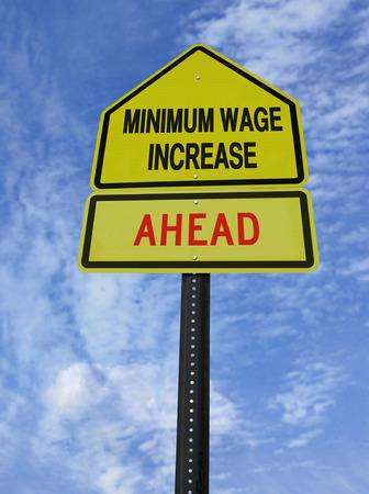 verhogen: conceptuele bord met woorden stijging van het minimumloon vooruit over de blauwe hemel Stockfoto