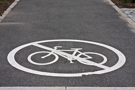 white painted sign for no bike line on asphalt pavement photo