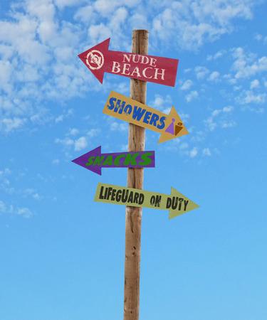 naaktstrand: houten vier pijl richting tekenen post naar het naakt strand, douches, snacks en een badmeester tegen een blauwe hemel Stockfoto