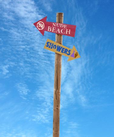 naaktstrand: houten pijl richting tekenen post naar het naakt strand en douches tegen een blauwe hemel