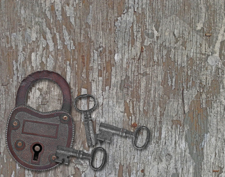 copper padlock and a keys on a weathered old wooden panel