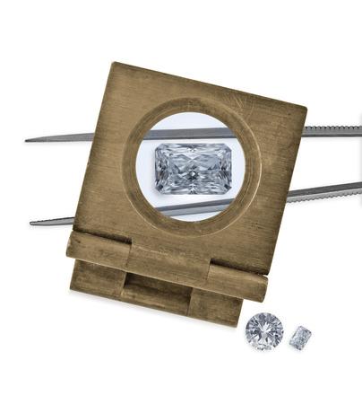 vintage loupe over diamond and tweezers, two diamonds on side photo