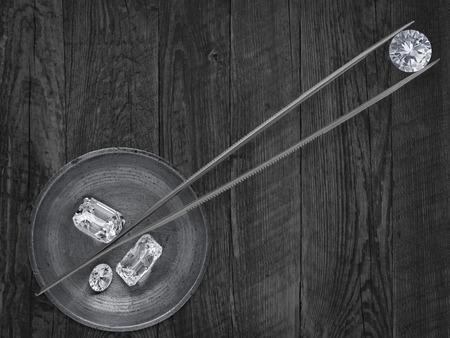 作業真鍮ちりとりとピンセットで様々 なカットのダイヤモンドのモノクロ イメージ