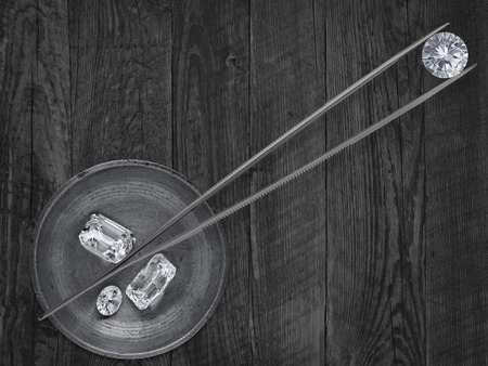 monochromatic image of a various cut  diamonds in a working  brass tray and  tweezers