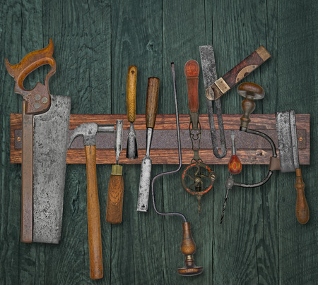 vintage woodworking tools on a magnetic rack against the wooden wall photo