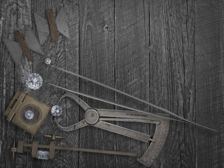faded colors vintage jewelers tools and diamonds over wooden bench, space for text photo