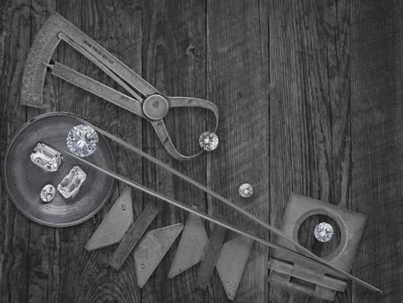 pinzas: imagen en blanco y negro de un Herramientas de joyería vintage y diamantes sobre banco de madera, espacio para el texto