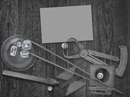 black and white image of a vintage jeweler tools and diamonds over wooden bench, blank card for your business photo