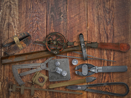 vintage jeweler tools and diamonds over wooden working bench, space for text