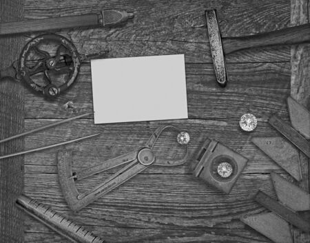 businesscard: black and white image of a vintage jeweler tools and diamonds over wooden bench, space for text on a blank businesscard