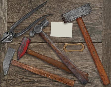 wrought iron: vintage blacksmith or metalwork tools over wooden bench, blank plate and business card for your text